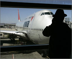 Travelers like this man waiting to board an NWA jet last month at Detroit Metropolitan are likely to see fewer flying options as airlines face rising fuel costs.