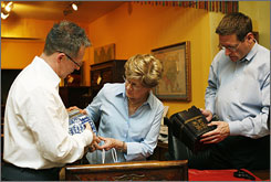 Silk Road Collection owners Donald St. Pierre, left, and Robert Turner help customer Claire Bergeron. The store got a business boost from its Web focus.