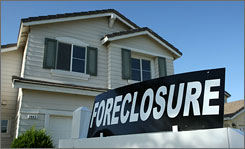 A foreclosure sign sits in front of a home for sale in Stockton, Calif.