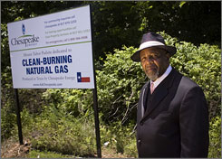 Pastor Elvis Bowman by a sign advertising natural gas production on property owned by his church, which will make thousands of dollars a month.