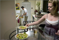 James Matthews, 26, and his wife, Rebecca, get set for another dinner at home. Because much of his pay comes in the form of commissions, Matthews, who works in financial services, now earns half what he was earning just last year.