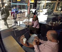Adam Sold uses wireless Internet access at a Starbucks in San Francisco. The chain is planning Wi-Fi freebies.