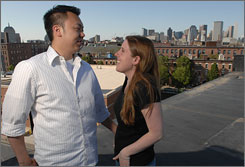 Abby Lesniak, 26, right, and her boyfriend, John Paul Nguyen, 28, on the roof of a Boston building where they have purchased a newly converted loft.