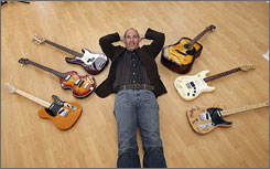 Jerry Gladstone with guitars signed by, clockwise from left, Bob Dylan, Paul McCartney, Brian Wilson, The Eagles, the Grateful Dead, the Rolling Stones.