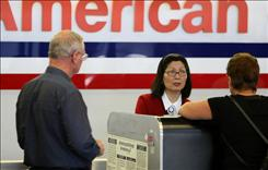 A ticket agent at San Francisco International helps customers check in for flights on Wednesday. Airfares are climbing, industry experts warn.