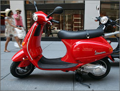 A scooter parked on a New York City sidewalk. U.S. sales of the pint-sized, gas-sipping vehicles have skyrocketed 66% in the first half of the year.