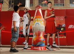 """Gao Zhen Feng, 22, looks over a display of Coke's """"Unity Bottle"""" featuring NBA stars LeBron James and Yao Ming at Coke's entertainment plaza in Beijing's Central Business District. The design eptomizes the modern multi-pronged digital ad strategy that feeds on mega-buzz."""