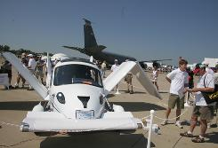 A Terrafugia Transition flying car on display July 28 at an airshow in Oshkosh, Wis., with its wings in a half-folded position. Its projected price is $194,000.