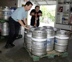 Tim Herzog, left, helps Paul Koehler push kegs into the cooler at Flying Bison Brewing in Buffalo