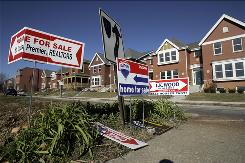 Signs advertising homes for sale stand in a median across from a row of new townhouses for sale in this Nov. 29, 2007, file photo, in St. Louis.