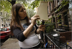Emily Ryan looks through trash on Manhattan's Upper West Side. Her apartment is full of finds such as a desk, filing cabinet, TV and decorative mirror.