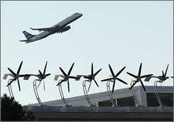 A jet passes over wind turbines at Boston Logan. There are 20 turbines so far that are expected to generate about 100,000 kilowatt-hours a year.