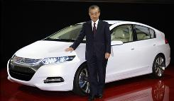 Honda's Takeo Fukui shows off a concept version of the new Insight gasoline-electric hybrid.