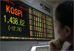 A Korean Stock Exchange worker watches stocks drop on Tuesday amid the U.S. financial crisis.
