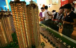 People view models of real estate units in Shaanxi Province. Despite China's wealth of cash, it is not expected to invest in U.S. financial institutions.