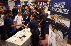 Denver police detective Sheri Duran hands out information at a job fair sponsored by the Colorado state government.
