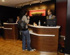 Jeremy McCluskey helps Shiva Barbosa of the U.K. check out at a Marriott Courtyard in Fairfax, Va.