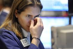 Specialist Jennifer Klesaris studies her monitors as she works on the floor of the New York Stock Exchange.