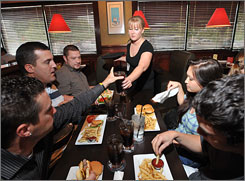 Beverly Nazaroff serves a table at a Ruby Tuesday in Fairfax, Va. From left are: Sage McGirk, Dave Welling, Jeremy Arther, Christine Reilly, Flip Bunts.