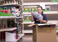 Angela Stanley stocks Christmas items at Wal-Mart in Rogers, Ark. 39% of Wal-Mart shoppers in a survey said they would shop earlier this holiday season.