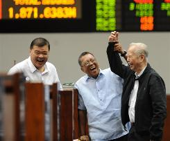 Traders smile at the Philippine Stock Exchange in Manila's financial district Tuesday.
