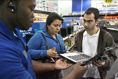 Narges Anbardar, middle, and Mani Jalilian shop for a laptop computer as Best Buy associate Greg Xavier tries to help them make their choice.