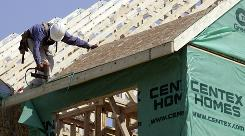 In this file photo, a construction worker nails plywood to the roof of a new home in Richmond, Va.