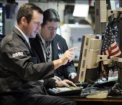 Specialists work on the floor of the New York Stock Exchange on Monday.