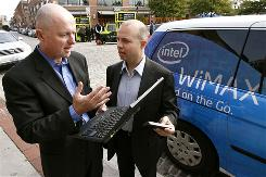 Sean Maloney, executive vice president of Intel, left, and Ben Wolff, CEO of Clearwire, demonstrate a laptop with Intel's WiMax module during the launch of Sprint Nextel's Xohm network in Baltimore.