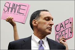 Protesters gather behind Richard Fuld of Lehman Bros. before his testimony on Capitol Hill that the largest bankruptcy in history was beyond his control.