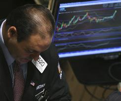 A trader works on the floor of the New York Stock Exchange, where stocks slid on Tuesday as recession fears fueled a sell-off in commodity-related companies.