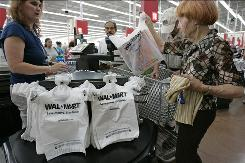 A customer checks out at Wal-Mart in San Jose, Calif., in August.