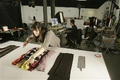 Stylist Jessica Mooney, foreground, and photographer Darren Ferriera, seated, work on holiday merchandise for Gap.com in San Francisco.