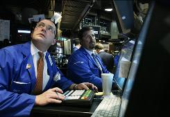 Specialists work at their terminals on the floor of the New York Stock Exchange.