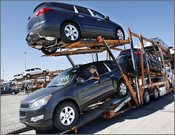 "Chevrolet Traverse vehicles are loaded onto a car carrier at GM's Spring Hill, Tenn., factory. ""It just feels like a matter of time"" before a Detroit automaker goes bankrupt, an industry analyst says."