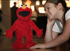 A girl watches the popular Elmo Live toy perform at the Dream Dream Toys exhibition in London.