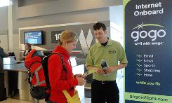 Passenger Emmaline Allwood learns about Aircell's in-flight broadband service Gogo from Jared Karns in JFK Airport's American Airlines terminal.