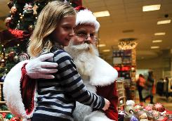 Joshua Kay, 8, of Leesburg, Va., sits on the lap of Santa Ken Traveller at Tysons Galleria in McLean, Va.