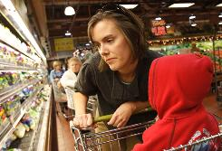 "Kelly Whalen, with son Aidan, one of her four children, shops for Thanksgiving dinner. She and husband Bob recently went on a ""spending diet."""