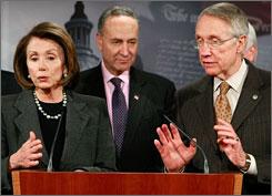 Sen. Charles Schumer, center, listens while House Speaker Nancy Pelosi, left, and Senate Majority Leader Harry Reid, right, speak during a news conference on Capitol Hill Thursday in Washington, D.C.