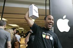 Kevin Edwards, of Palo Alto, Calif., celebrates as he holds up his new Apple iPhone 3G on July 11.
