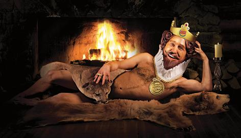 The Burger King King poses in front of a fireplace wrapped in animal skin to promote the new men's body spray Flame.