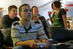 Eric Ospina plays video games as the grown-ups gab at a party to promote Microsoft's Xbox in Yonkers, N.Y.
