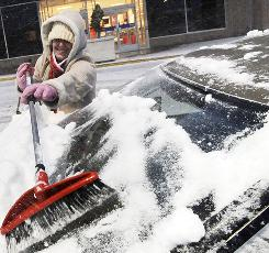 Shannon LaBonte, a store employee at the Northshore Mall in Peabody, Mass., removes snow from her windshield after a winter storm last week.