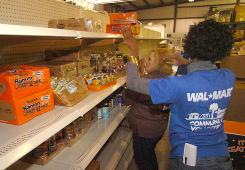 A Wal-Mart associate and food bank volunteer stock a community food bank shelf as part of the retailer's national food donation program.