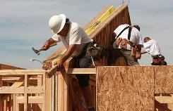 Construction workers build the frame of a house at a new development in Hayward, Calif. The housing sector is expected to improve, but it will probably take awhile.