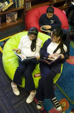 Jennifer Luna, left, Manuel Alvarez, back, and Gabriela DeLuna read at one of the newly remodeled libraries at Philip D. Armour School in Chicago. Target did the remodeling.