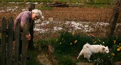 Nurse and midwife Peggy Kemner wraps up her gardening for the evening with her dog Fluffy at her side.