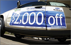 A sign hangs on the side of an unsold 2008 Outback to promote the discount available on the vehicle at a Subaru dealership in the southeast Denver suburb of Centennial, Colo. in November.