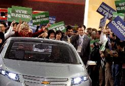 Michigan Gov. Jennifer Granholm (red dress) marches with auto workers and others behind a Chevy Volt electric vehicle during the introduction of General Motors' vehicles at the press preview for the Detroit auto show.